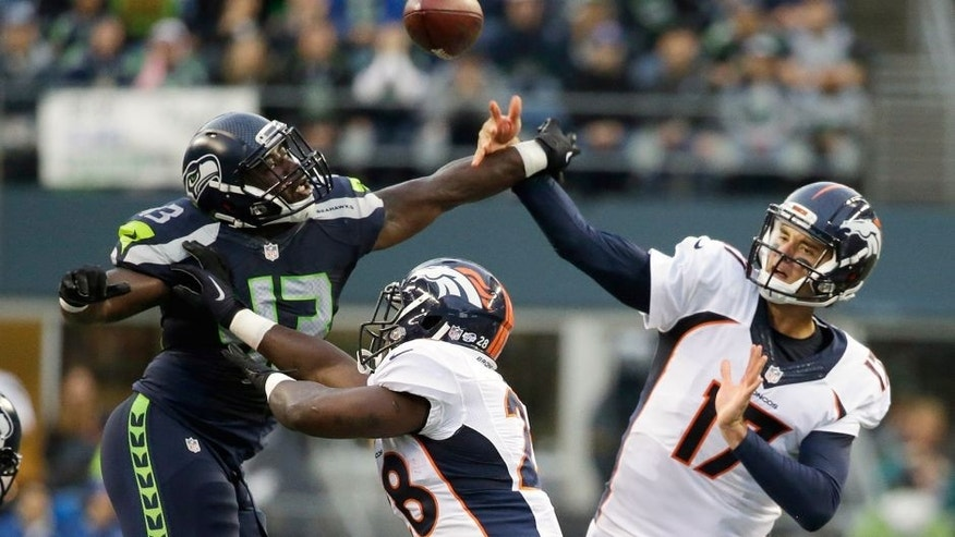 Seattle Seahawks linebacker Quayshawn Nealy (43) tries to deflect a pass by Denver Broncos quarterback Brock Osweiler (17) as Broncos running back Montee Ball, center, blocks. during the first half of a preseason NFL football game, Friday, Aug. 14, 2015, in Seattle. (AP Photo/Elaine Thompson)