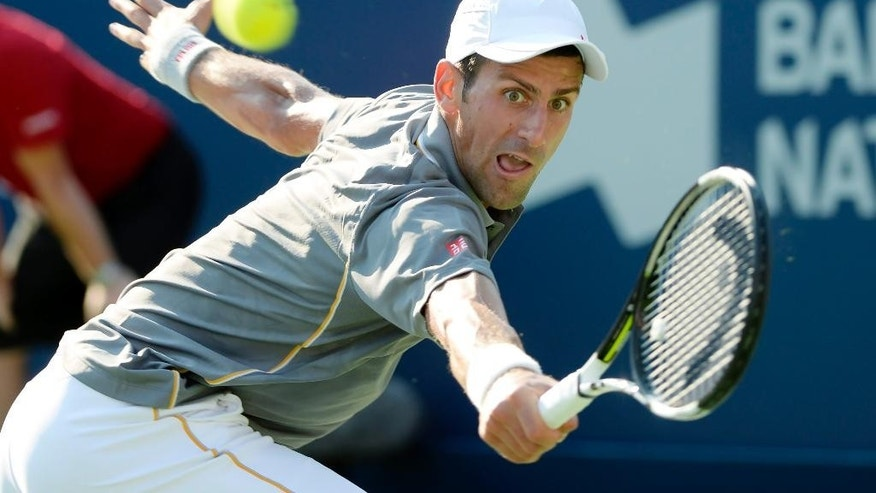Novak Djokovic, of Serbia, hits a return to Andy Murray, of Great Britain, during the men's final at the Rogers Cup tennis tournament in Montreal on Sunday, Aug. 16, 2015. (Paul Chiasson/The Canadian Press via AP)