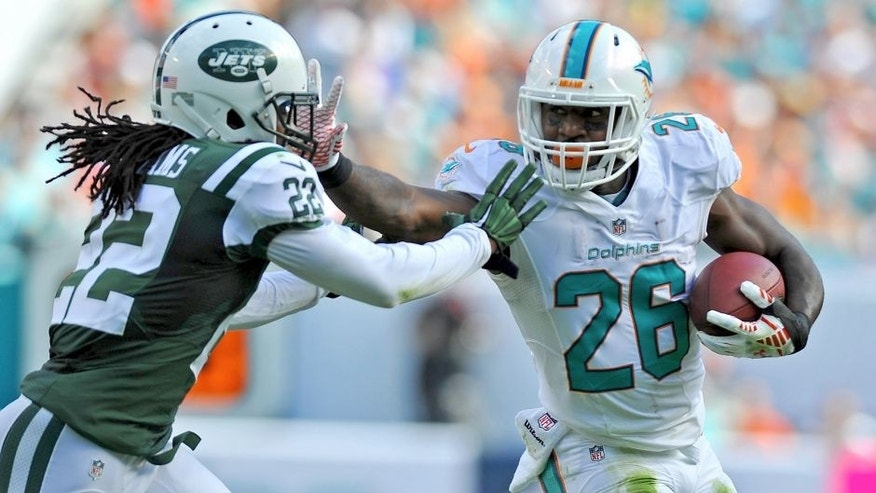 Dec 28, 2014; Miami Gardens, FL, USA; Miami Dolphins running back Lamar Miller (26) stiff arms New York Jets cornerback Marcus Williams (22) during the first half at Sun Life Stadium. Mandatory Credit: Steve Mitchell-USA TODAY Sports
