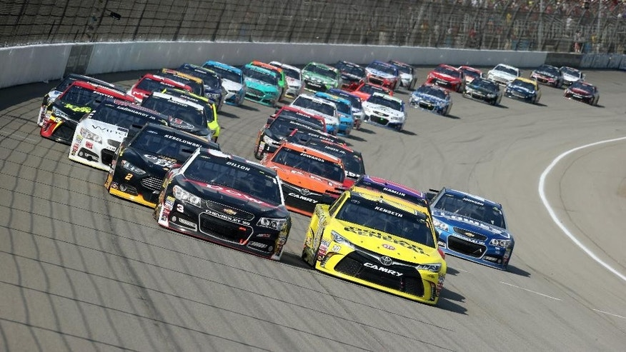 Austin Dillon, left, and Matt Kenseth lead the pack through the first turn during the NASCAR Sprint Cup series auto race at Michigan International Speedway, Sunday, Aug. 16, 2015, in Brooklyn, Mich. (AP Photo/Bob Brodbeck)