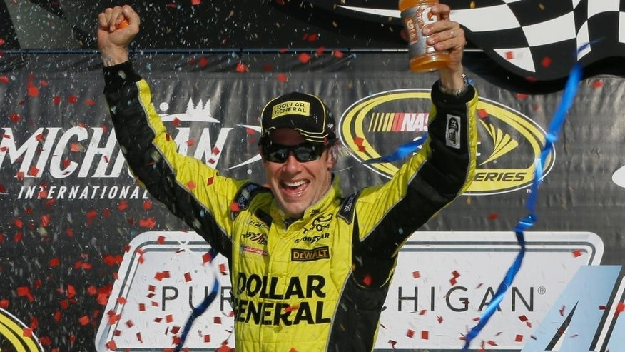 Matt Kenseth raises his arms in victory lane after winning the NASCAR Sprint Cup series auto race at Michigan International Speedway, Sunday, Aug. 16, 2015, in Brooklyn, Mich. (AP Photo/Carlos Osorio)