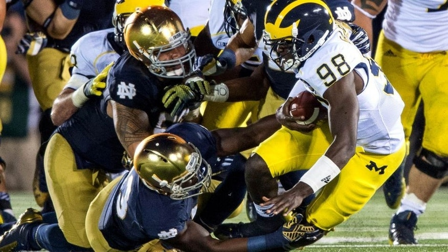 Sep 6, 2014; South Bend, IN, USA; Michigan Wolverines quarterback Devin Gardner (98) is sacked by Notre Dame Fighting Irish linebacker Kolin Hill (43) defensive lineman Justin Utupo (53) and cornerback Matthias Farley (41) in the fourth quarter at Notre Dame Stadium. Notre Dame won 31-0. Mandatory Credit: Matt Cashore-USA TODAY Sports