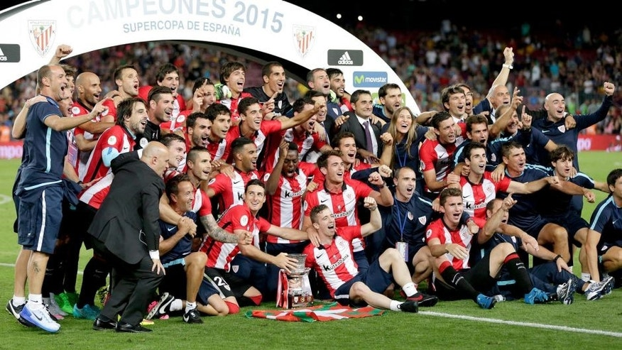 Bilbao teammates celebrate with the trophy after the second leg Spanish Super Cup soccer match between FC Barcelona and Athletic Bilbao at the Camp Nou stadium in Barcelona, Spain, Monday, Aug.17, 2015. (AP Photo/Emilio Morenatti)