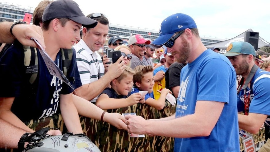 FORT WORTH, TX - APRIL 11: Dale Earnhardt Jr., driver of the #88 Nationwide Chevrolet, right, signs his autgraph for fans on the red carpet prior to the drivers meeting for the NASCAR Sprint Cup Series Duck Commander 500 at Texas Motor Speedway on April 11, 2015 in Fort Worth, Texas. (Photo by Sarah Glenn/Getty Images for Texas Motor Speedway)