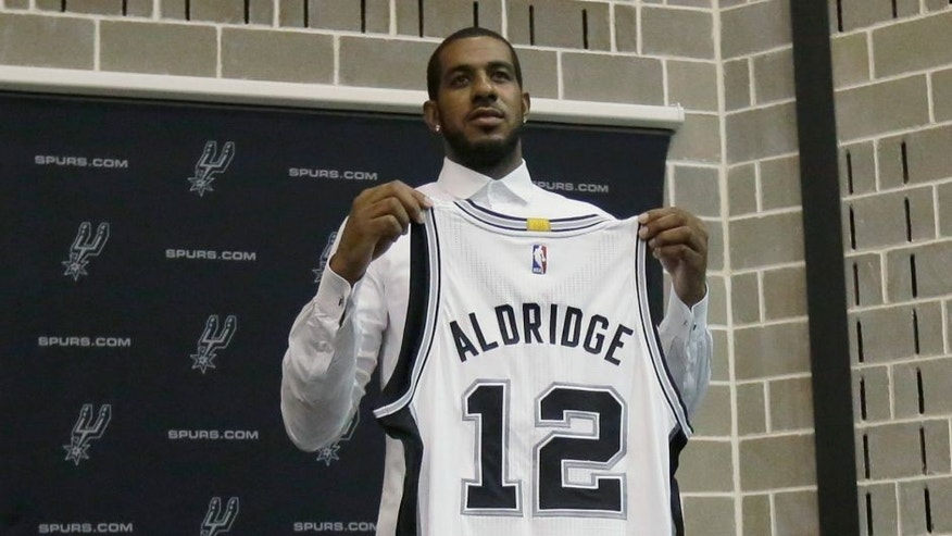 LaMarcus Aldridge poses with his new jersey following a news conference at the team's practice facility where he was formally introduced after he signed with the San Antonio Spurs NBA basketball team, Friday, July 10, 2015, in San Antonio. (AP Photo/Eric Gay)