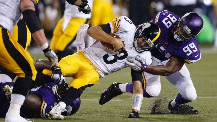 Pittsburgh Steelers quarterback Landry Jones is tackled by Minnesota Vikings defensive end Danielle Hunter (right) and defensive tackle Shamar Stephen (bottom left) after scrambling for a short gain during the second half of an NFL preseason football game in Canton, Ohio, on Sunday, August 9, 2015.