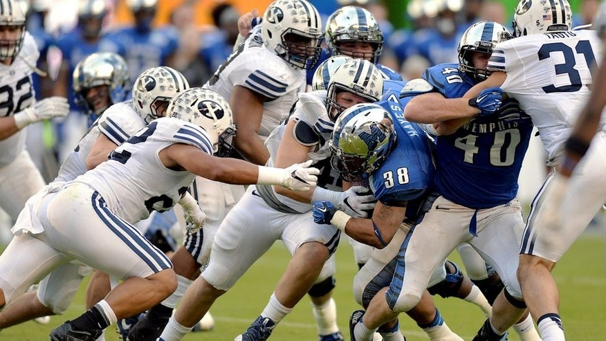 Dec 22, 2014; Miami, FL, USA; Memphis Tigers running back Brandon Hayes (38) is tackled by Brigham Young Cougars defense during the third quarter in the Miami Beach Bowl at Marlins Park. Memphis won 55-48 in a double overtime. Mandatory Credit: Steve Mitchell-USA TODAY Sports