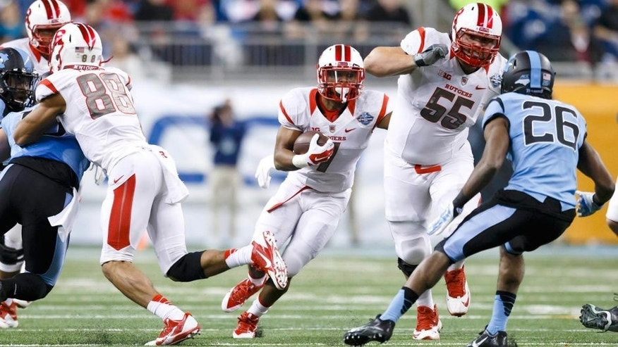 Dec 26, 2014; Detroit, MI, USA; Rutgers Scarlet Knights running back Robert Martin (7) runs the ball while offensive lineman Betim Bujari (55) blocks North Carolina Tar Heels safety Dominquie Green (26) in the first quarter in the 2014 Quick Lane Bowl at Ford Field. Mandatory Credit: Rick Osentoski-USA TODAY Sports