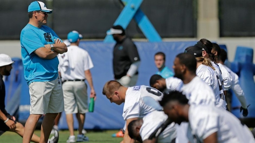 Carolina Panthers head coach Ron Rivera, left, watches players warm up during a practice at the NFL football team's rookie minicamp in Charlotte, N.C., Friday, May 8, 2015. (AP Photo/Chuck Burton)