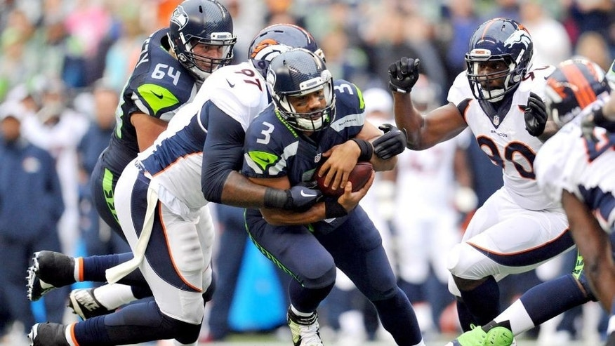 August 14, 2015; Seattle, WA, USA; Denver Broncos defensive tackle Malik Jackson (97) and defensive end Antonio Smith (90) bring down Seattle Seahawks quarterback Russell Wilson (3) during the first half in a preseason NFL football game at CenturyLink Field. Mandatory Credit: Gary A. Vasquez-USA TODAY Sports