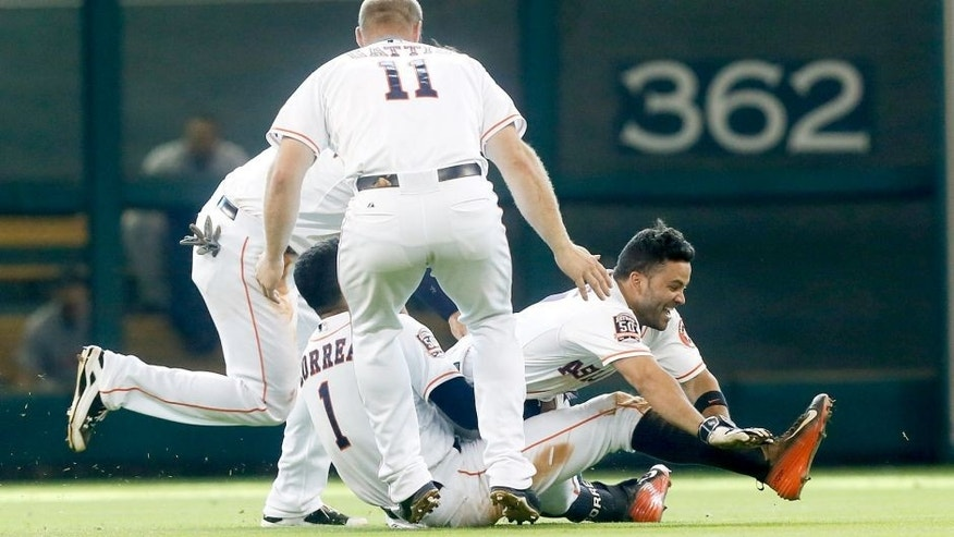 HOUSTON, TX - AUGUST 16: Jose Altuve #27 of the Houston Astros celebrates with Carlos Correa, Evan Gattis #11 and Jake Marisnick #6 after hitting walkoff single to beat the Detroit Tigers 6-5 at Minute Maid Park on August 16, 2015 in Houston, Texas. (Photo by Bob Levey/Getty Images)