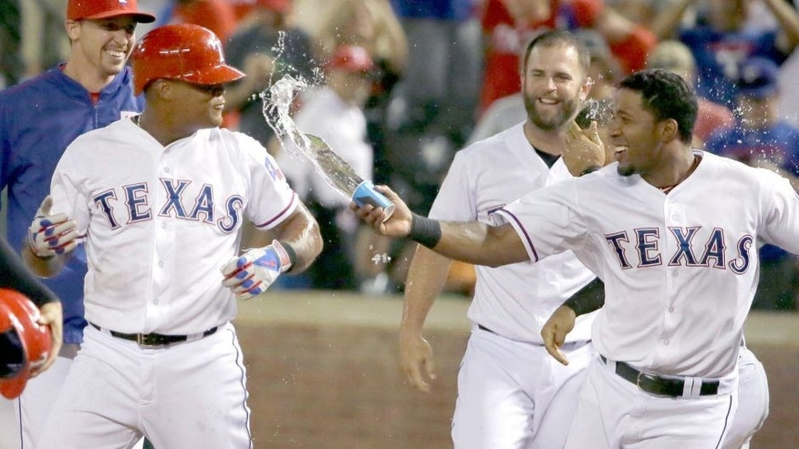 Texas Rangers Elvis Andrus, right, tosses water at teammate Adrian Beltre to celebrates Betran's bases loaded walk during the ninth inning of a baseball game against the Seattle Mariners in Arlington, Texas, Monday, Aug. 17, 2015. Rangers Ryan Strausborger scored on the play giving the Rangers the 4-3 win. (AP Photo/LM Otero)