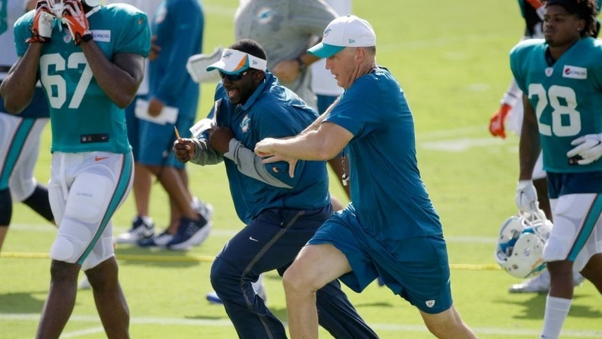 Miami Dolphins head coach Joe Philbin, foreground center, races assistant defensive backs coach Blue Adams as they change practice fields at the teams NFL football training camp, Wednesday, Aug. 5, 2015 in Davie, Fla. (AP Photo/Wilfredo Lee)