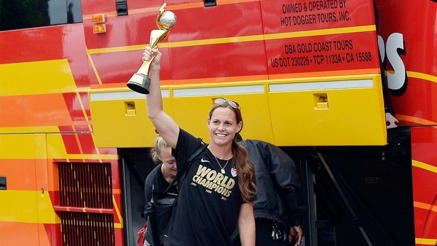 LOS ANGELES, CA - JULY 6: Captain Christie Rampone holds the FIFA Women's World Cup trophy as she walks to the bus after arriving at Los Angeles International Airport July 6, 2015 in Los Angeles, California. (Photo by Kevork Djansezian/Getty Images)