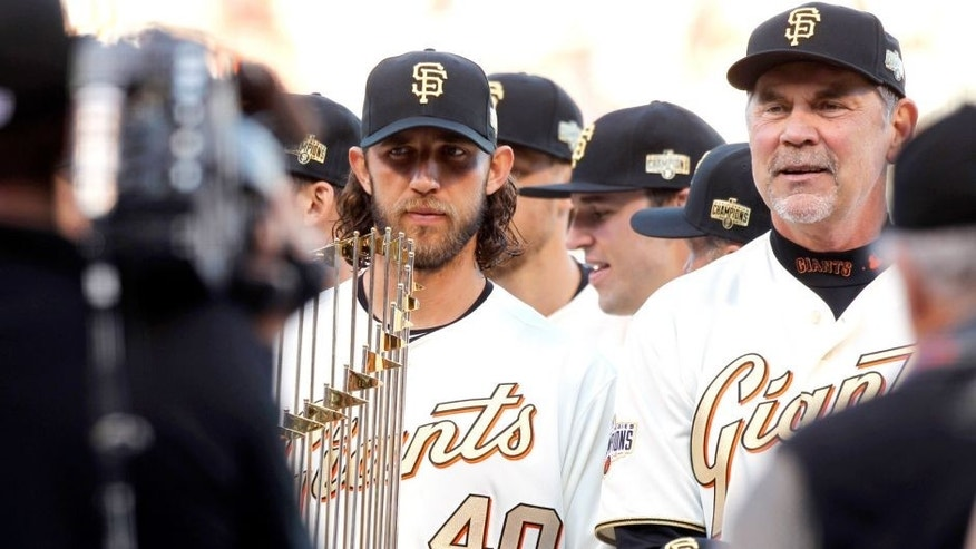 Apr 18, 2015; San Francisco, CA, USA; San Francisco Giants pitcher Madison Bumgarner (40) holds onto a World Series trophy during the 2014 World Championship Ring Ceremony before the start of the game against the Arizona Diamondbacks at AT&T Park. Mandatory Credit: Cary Edmondson-USA TODAY Sports