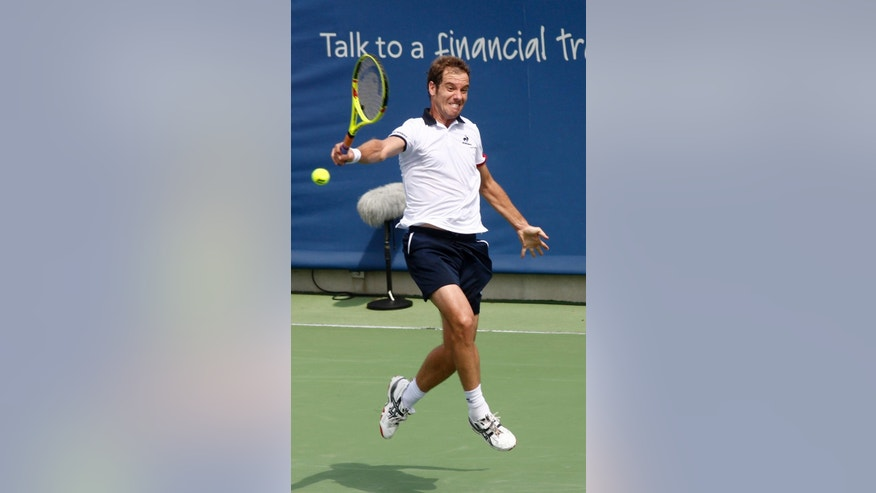Richard Gasquet, of France, returns a volley from Nick Kyrgios, of Australia, during a first round match at the Western & Southern Open tennis tournament, Tuesday, Aug. 18, 2015, in Mason, Ohio. (AP Photo/David Kohl)