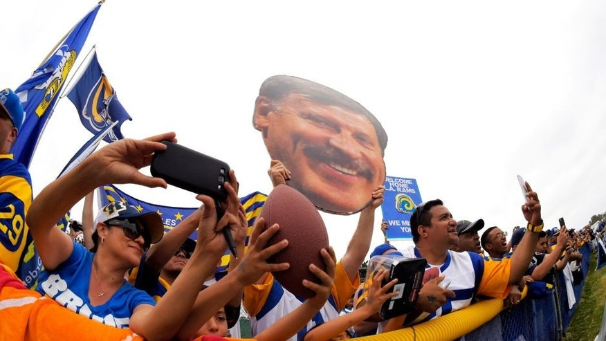 Fans watch the St. Louis Rams and the Dallas Cowboys participate in a joint NFL football training camp as one holds up a picture of Rans owner Stan Kroenke, Monday, Aug. 17, 2015, in Oxnard, Calif. (AP Photo/Mark J. Terrill)