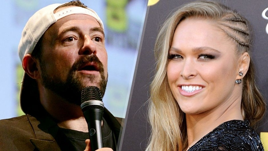 SAN DIEGO, CA - JULY 10: Filmmaker Kevin Smith speaks onstage at the 'Yoga Hosers' panel during Comic-Con International 2015 at the San Diego Convention Center on July 10, 2015 in San Diego, California. (Photo by Albert L. Ortega/Getty Images) WESTWOOD, CA - JUNE 01: Ronda Rousey arrives at Warner Bros. Pictures Premiere of 'Entourage' at Regency Village Theatre on June 1, 2015 in Westwood, California. (Photo by Barry King/Getty Images)