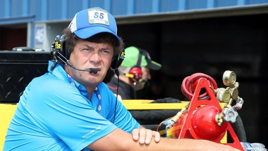 FILE- In this Aug. 14, 2015, file photo, team owner Michael Waltrip watches from outside his garage before a practice session for the NASCAR Sprint Cup series auto race at Michigan International Speedway in Brooklyn, Mich. Waltrip's rocky nine-year effort to build a successful race team was on the verge of collapse Wednesday, Aug. 19, 2015, as the organization said it will not run any cars full-time next season. Driver Clint Bowyer was given a release from his contract to pursue a new job for 2016. (AP Photo/Bob Brodbeck, File)