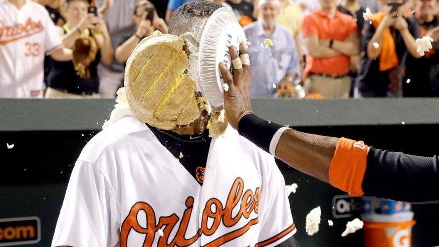 Baltimore Orioles' Henry Urrutia is hit in the face with a pie by teammate Adam Jones after a baseball game against the New York Mets, Wednesday, Aug. 19, 2015, in Baltimore. Urrutia hit a solo home run in the ninth to give Baltimore a 5-4 win. (AP Photo/Patrick Semansky)
