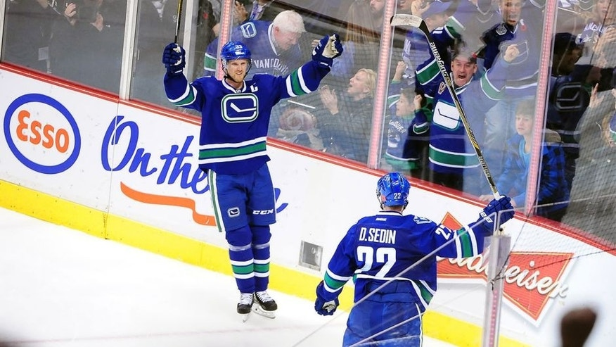 Nov 11, 2014; Vancouver, British Columbia, CAN; Vancouver Canucks forward Henrik Sedin (33) celebrates with forward Daniel Sedin (22) for a goal against Ottawa Senators goaltender Craig Anderson (41) (not pictured) during the overtime at Rogers Arena. The Vancouver Canucks won 4-3 in overtime. Mandatory Credit: Anne-Marie Sorvin-USA TODAY Sports