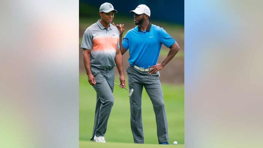 Tiger Woods, left, chats on the first green with Los Angeles Clippers basketball player Chris Paul during the pro-am at the Wyndham Championship golf tournament, Wednesday, Aug. 19, 2015, at Sedgefield Country Club in Greensboro, N.C. (AP Photo/Rob Brown)