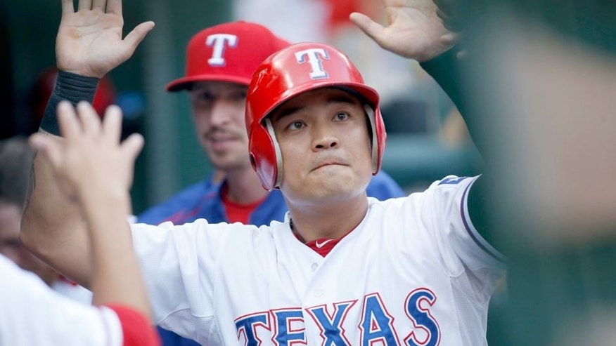Aug 17, 2015; Arlington, TX, USA; Texas Rangers right fielder Shin-Soo Choo (17) is congratulated by his teammates in the dugout after scoring a run in the first inning against the Seattle Mariners at Globe Life Park in Arlington. Mandatory Credit: Tim Heitman-USA TODAY Sports