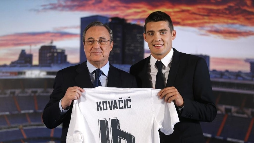 Real Madrid's new soccer player Mateo Kovacic, right, poses with club President Florentino Perez during his official presentation to the media at the Santiago Bernabeu stadium in Madrid, Spain, Wednesday, Aug. 19, 2015. Kovacic, who played dor  Italian Inter Milan team, has signed a contract for six seasons. (AP Photo/Francisco Seco)