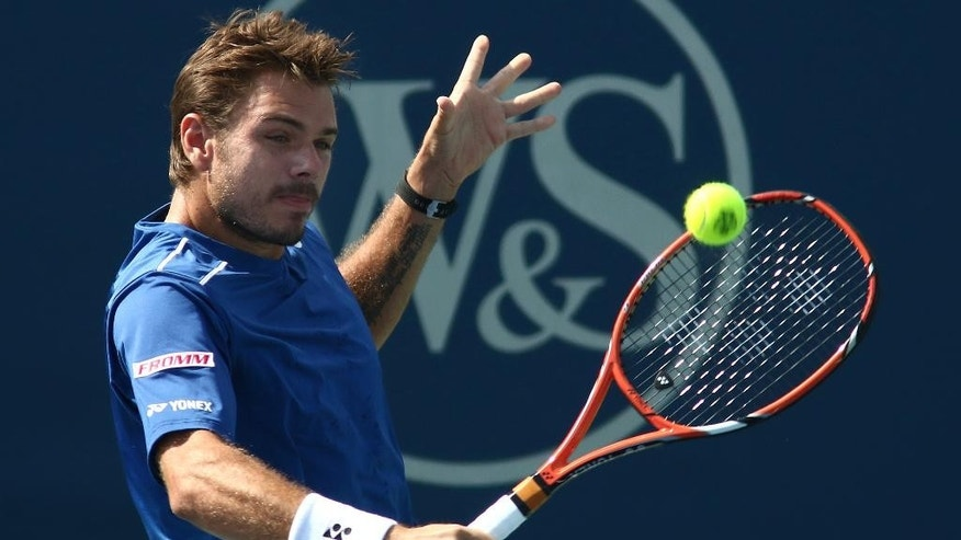 Stan Wawrinka, of Switzerland, returns the ball to Ivo Karlovic, of Croatia, at the Western & Southern Open tennis tournament, Thursday, Aug. 20, 2015, in Mason, Ohio. (AP Photo/Tom Uhlman)