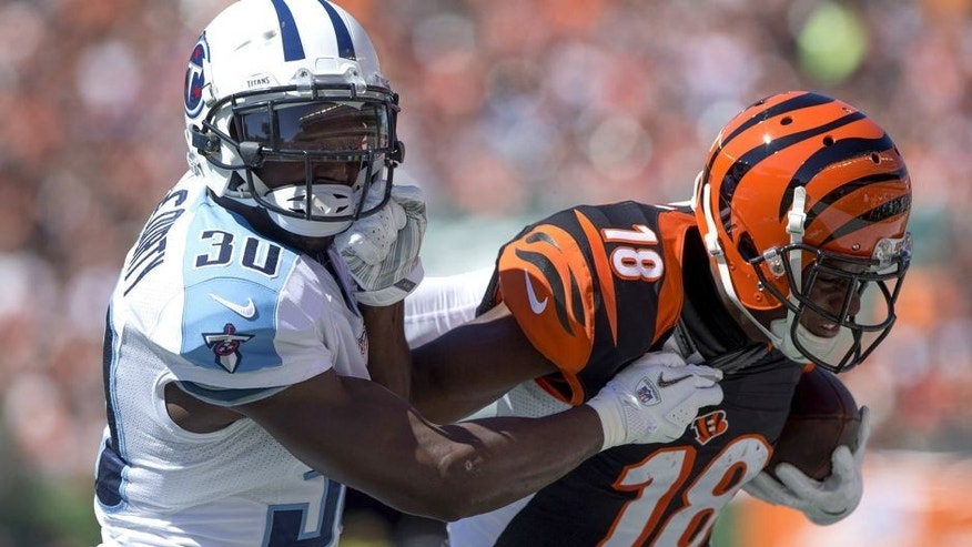 Sep 21, 2014; Cincinnati, OH, USA; Tennessee Titans cornerback Jason McCourty (30) tackles Cincinnati Bengals wide receiver A.J. Green (18) during the first half at Paul Brown Stadium. Mandatory Credit: Aaron Doster-USA TODAY Sports