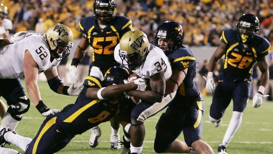<p>November 25, 2011; Morgantown,WV, USA: Pittsburgh Panthers running back Issac Bennett (34) scores a touchdown against West Virginia Mountaineers defenders Keith Tandy (8) and Jared Barber (right) during the first quarter at Milan Puskar Stadium. Mandatory Credit: Charles LeClaire-USPRESSWIRE</p>
