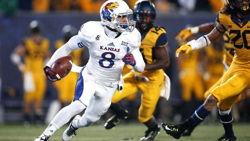 Oct 4, 2014; Morgantown, WV, USA; Kansas Jayhawks wide receiver Nick Harwell (8) runs with the ball on a seventy-six yard punt return for a touchdown against the West Virginia Mountaineers during the fourth quarter at Milan Puskar Stadium. The Mountaineers won 33-14. Mandatory Credit: Charles LeClaire-USA TODAY Sports