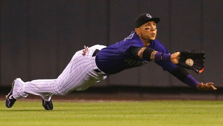 DENVER, CO - AUGUST 20: Right fielder Carlos Gonzalez #5 of the Colorado Rockies makes a diving catch to rob Jayson Werth of the Washington Nationals of a single in the eighth inning at Coors Field on August 20, 2015 in Denver, Colorado. (Photo by Justin Edmonds/Getty Images)
