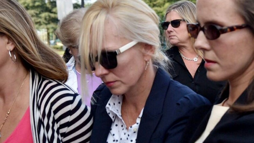 Molly Shattuck, second from right foreground, arrives at the Sussex County Courthouse in Georgetown, Del., for sentencing, Friday, Aug. 21, 2015. Former Baltimore Ravens cheerleader Molly Shattuck has been sentenced to two years of probation after pleading guilty to raping a 15-year-old boy at a vacation rental home in Delaware. The 48-year-old collapsed to her knees after she was sentenced Friday morning and wept as she apologized. (Kim Hairston/The Baltimore Sun via AP) WASHINGTON EXAMINER OUT; MANDATORY CREDIT