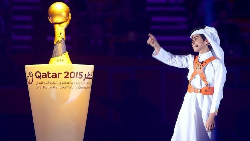 A young boy points to the trophy during the podium ceremony of 24th Men's Handball World Championships at the Lusail Multipurpose Hall in Doha on February 1, 2015. France became the first team in handball history to win five world championships when they beat surprise finalists Qatar 25-22. AFP PHOTO / MARWAN NAAMANI (Photo credit should read MARWAN NAAMANI/AFP/Getty Images)