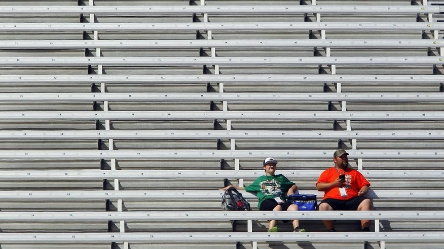 Fans sit in the stands during practice for the Food City 300 NASCAR Xfinity Series auto race on Friday, Aug. 21, 2015 in Bristol, Tenn. (AP Photo/Wade Payne)