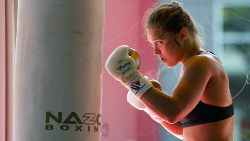 FILE - This July 15, 2015, file photo shows mixed martial arts fighter Ronda Rousey working out at Glendale Fighting Club in Glendale, Calif. Rousey's star power grows with each month, and the UFC's dominant bantamweight champion could have held her next title defense anywhere. She chose to travel to Bethe Correia's native Brazil for UFC 190 on Saturday, Aug. 1,  just so she can embarrass the challenger in front of her home fans. (AP Photo/Jae C. Hong,File)