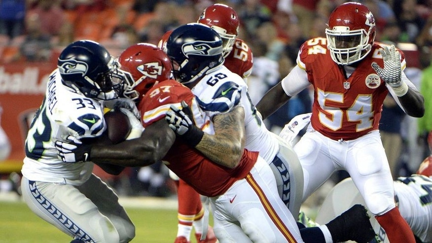 Aug 21, 2015; Kansas City, MO, USA; Seattle Seahawks running back Christine Michael (33) is tackled by Kansas City Chiefs defensive end Allen Bailey (97) in the first half at Arrowhead Stadium. Mandatory Credit: John Rieger-USA TODAY Sports