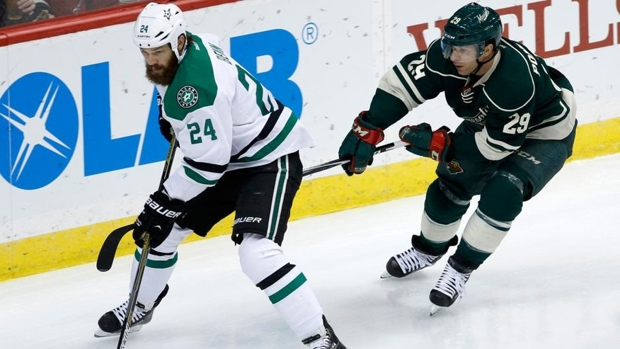 <p>Dallas Stars defenseman Jordie Benn (24) controls the puck in front of Minnesota Wild right wing Jason Pominville (29) during the first period of an NHL hockey game in St. Paul, Minn., Saturday, Nov. 1, 2014. (AP Photo/Ann Heisenfelt)</p>
