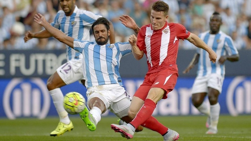 Malaga's Argentinian defender Marcos Alberto Angeleri (L) vies with Sevilla's French forward Kevin Gameiro during the Spanish league football match Malaga CF vs Sevilla FC at La Rosaleda stadium in Malaga on August 21, 2015. AFP PHOTO / JORGE GUERRERO (Photo credit should read Jorge Guerrero/AFP/Getty Images)