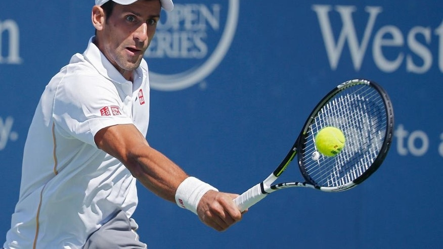 Novak Djokovic, of Serbia, returns the ball to Stanislas Wawrinka, of Switzerland, during a quarterfinal match at the Western & Southern Open tennis tournament, Friday, Aug. 21, 2015, in Mason, Ohio. (AP Photo/John Minchillo)
