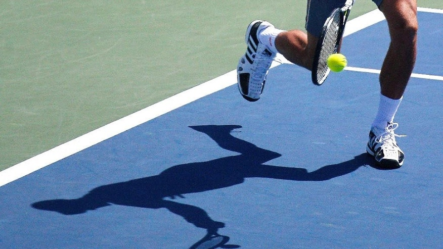 Novak Djokovic, of Serbia, returns the ball to Stanislas Wawrinka, of Switzerland, during a quarterfinal match at the Western & Southern Open tennis tournament, Friday, Aug. 21, 2015, in Mason, Ohio. Djokovic defeated Wawrinka 6-4, 6-1. (AP Photo/John Minchillo)