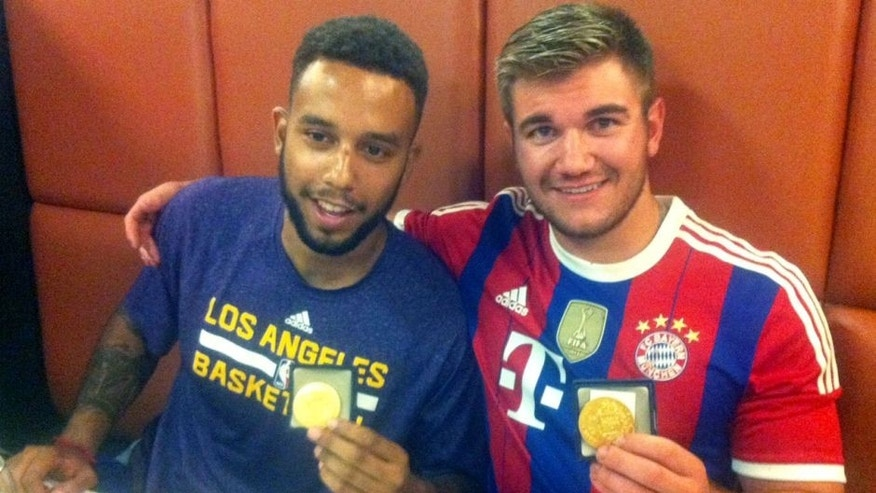 Anthony Sadler (L), from Pittsburg, California, and Alek Skarlatos from Roseburg, Oregon, hold their medals as they sit in a restaurant after a brief ceremony in the town of Arras, northern France, on August 21, 2015. The American servicemen overpowered a gunman armed with a Kalashnikov who opened fire on a high-speed train travelling from Amsterdam to Paris on August 21, 2015. AFP PHOTO / STRINGER (Photo credit should read -/AFP/Getty Images)