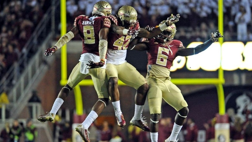 Nov 29, 2014; Tallahassee, FL, USA; Florida State Seminoles defensive back Jalen Ramsey (8), defensive back Lamarcus Brutus (42), and cornerback Nick Waisome (6) celebrate during the game against the Florida Gators at Doak Campbell Stadium. Mandatory Credit: Melina Vastola-USA TODAY Sports