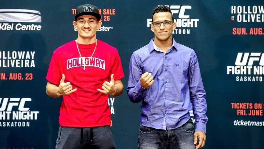 SASKATOON, SK - JUNE 24: Max Holloway (L) and Charles Oliveira (R) square off for the crowd at a press conference at the SaskTel Centre, June 24, 2015 in Saskatoon, Saskatchewan, Canada. (Photo by Steve Hiscock/Getty images)