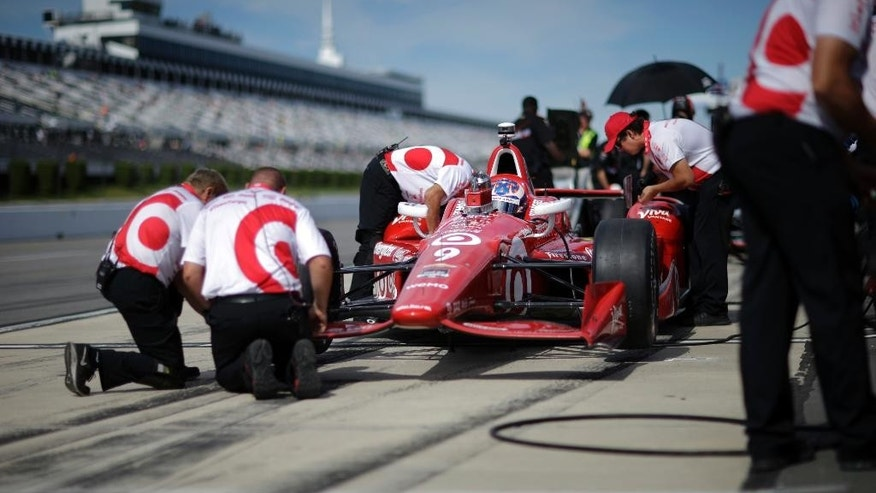 Scott Dixon, of New Zealand (9) waits as crew members work on his race car during practice for Sunday's Pocono IndyCar 500 auto race Saturday, Aug. 22, 2015, in Long Pond, Pa. (AP Photo/Mel Evans)