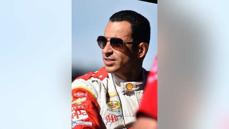 Helio Castroneves, of Brazil, stands on pit road during practice for Sunday's Pocono IndyCar 500 auto race , Saturday, Aug. 22, 2015, in Long Pond, Pa. (AP Photo/Derik Hamilton)