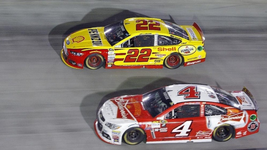Joey Logano (22) and Kevin Harvick (4) go into a turn during the NASCAR Sprint Cup Series auto race, Saturday, Aug. 22, 2015, in Bristol, Tenn. Logano won the race and Harvick was second. (AP Photo/Wade Payne)