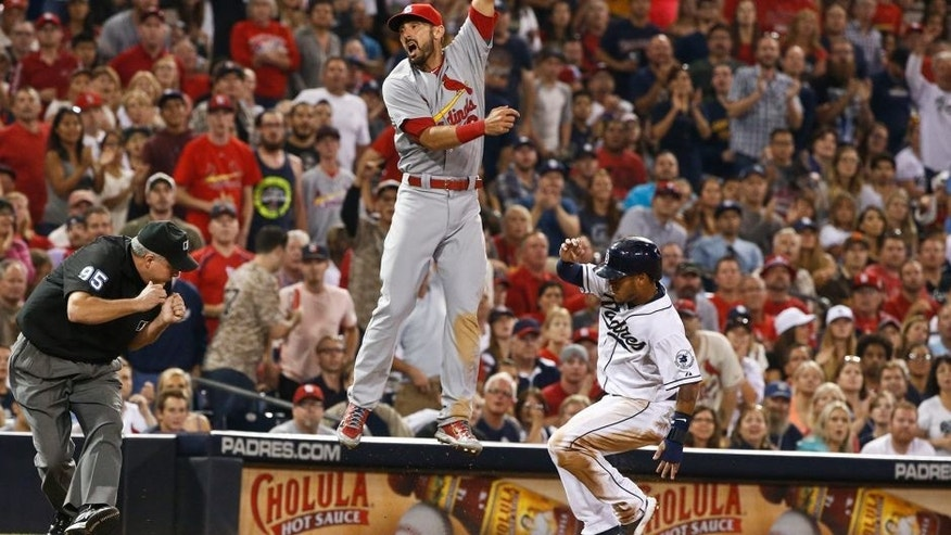 St. Louis Cardinals third baseman Matt Carpenter leaps in vain for a wild throw from the outfield as San Diego Padres' Alexi Amarista arrives at third during the fifth inning of a baseball game Friday, Aug. 21, 2015, in San Diego. The ball went into the dugout and Amarista scored. (AP Photo/Lenny Ignelzi)