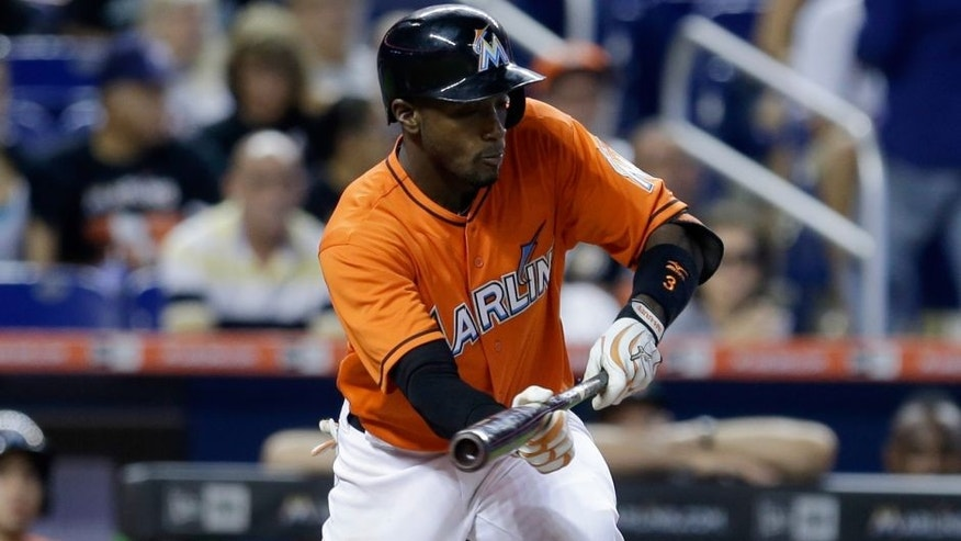Miami Marlins' Adeiny Hechavarria (3) bunts against the Philadelphia Phillies in the fifth inning of a baseball game, Sunday, Aug. 23, 2015, in Miami. Hechavarria was safe at first base. (AP Photo/Alan Diaz)